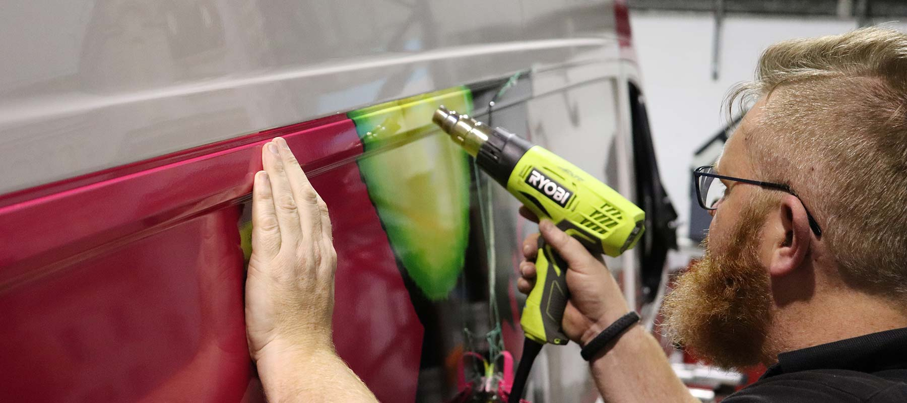 Man applying 3M wrapper to vehicle